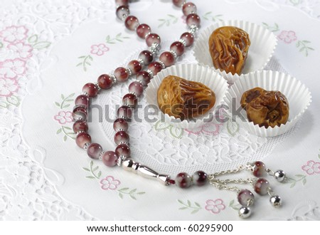 Dates in paper cups with islamic rosary. - stock photo