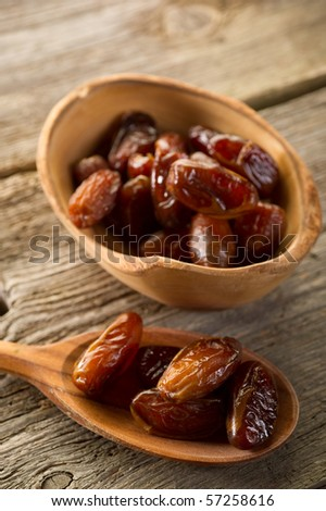 dates over spoon on wood background - stock photo