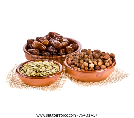 Dates, pumpkin seeds and hazelnuts in ceramic dishes isolated on white background - stock photo