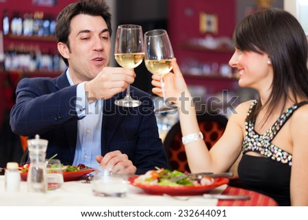 Dating concept, couple drinking wine in a restaurant - stock photo