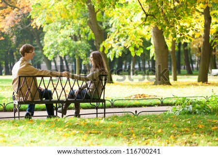 Dating couple on a bench by fall - stock photo
