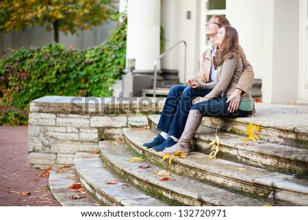 Dating couple sitting on the stairs - stock photo