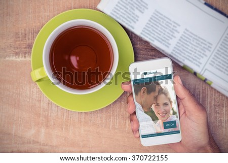 Dating website against cropped image of man holding smart phone - stock photo