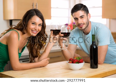 Dating with a bottle of red wine cheers and make a toast with glasses and happy smiles - stock photo