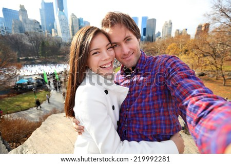 Dating young couple happy in love taking self-portrait selfie photo in Central Park, New York City in late fall early winter with skating rink in background. Tourists having fun date, Manhattan, USA. - stock photo