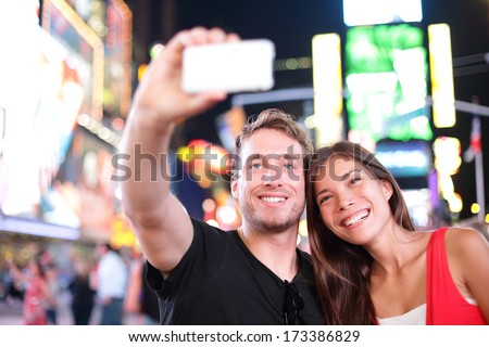 Dating young couple happy in love taking selfie self-portrait photo on Times Square, New York City at night. Beautiful young tourists having fun date, Manhattan, USA. Asian woman, Caucasian man - stock photo