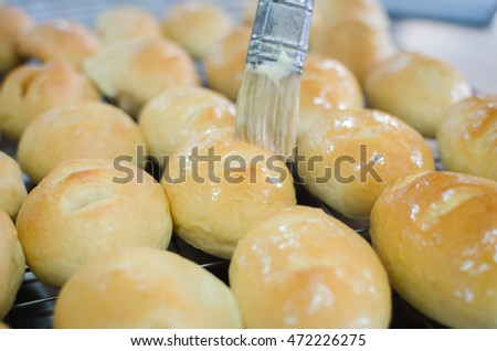 daubing butter to baked bun for shine its surface
