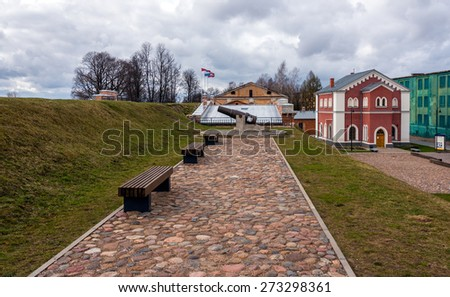 DAUGAVPILS, LATVIA - APRIL 12, 2015:Benches and sculpture of cannon in Daugavpils fortress in Latvia - stock photo