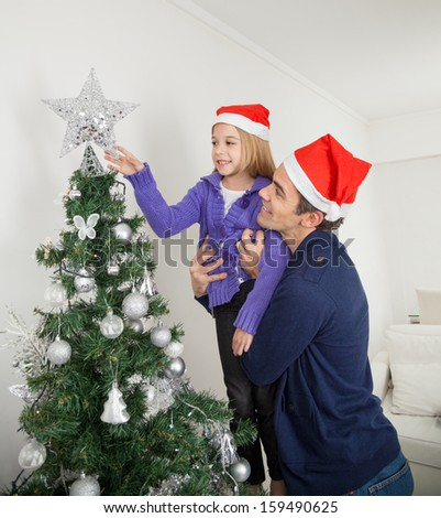 Daughter adjusting star on Christmas tree while being carried by father at home - stock photo