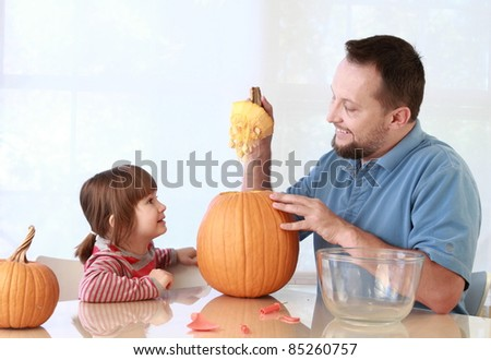 Daughter and father carving pumpkin for Halloween - stock photo