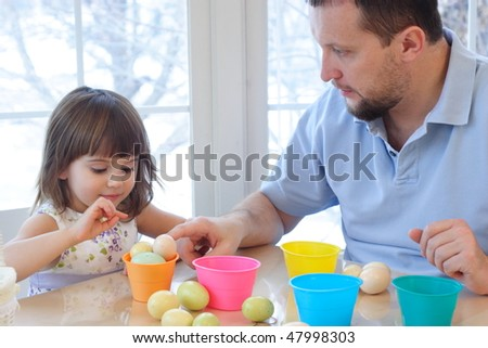 Daughter and father coloring eggs for Easter holiday