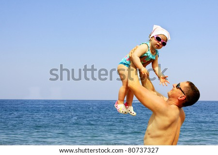 Daughter and father having fun on the beach - stock photo