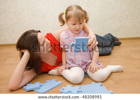 Daughter and her mother are solving puzzle - stock photo
