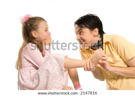 daughter and mom playing tickle on the feet - stock photo