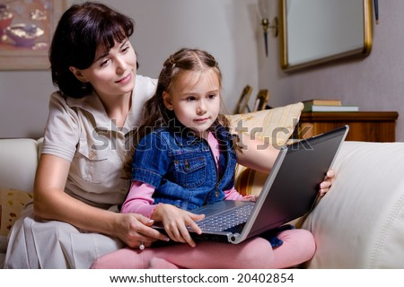daughter and mom with a notebook surfing internet