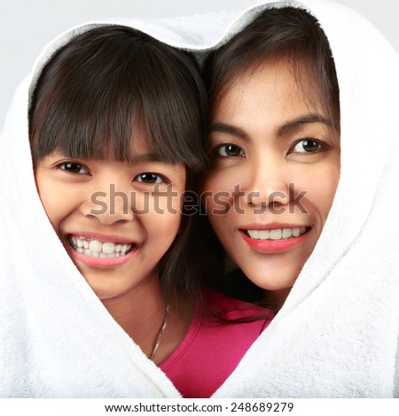 Daughter and mother are happy together under the sheets in bedroom - stock photo