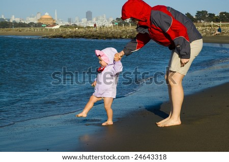 Daughter and mother are playing in the water on a cold sunny spring day with San Francisco skyline in the background. - stock photo