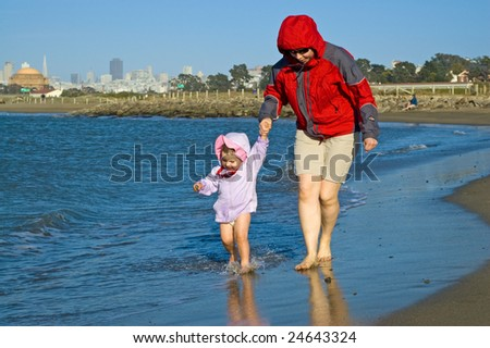 Daughter and mother are walking barefoot in the water on a cold sunny spring day with San Francisco skyline in the background. - stock photo
