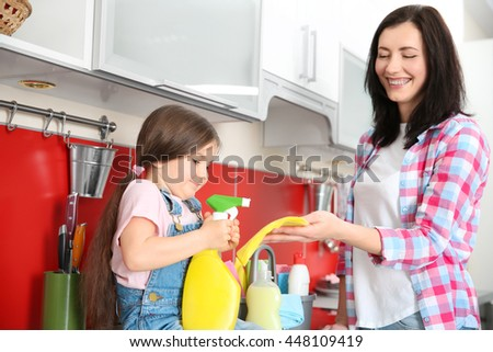 Daughter and mother cleaning kitchen - stock photo