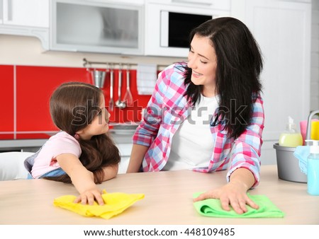 Daughter and mother cleaning kitchen table - stock photo
