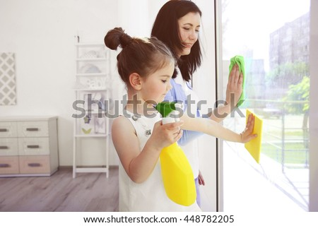Daughter and mother cleaning window together - stock photo