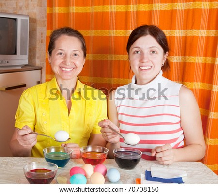 Daughter and mother coloring eggs for Easter holiday - stock photo