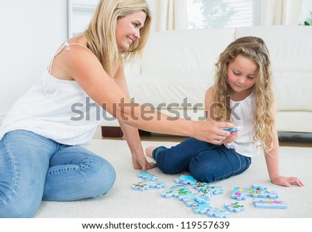 Daughter and mother doing a jigsaw puzzle on the floor - stock photo