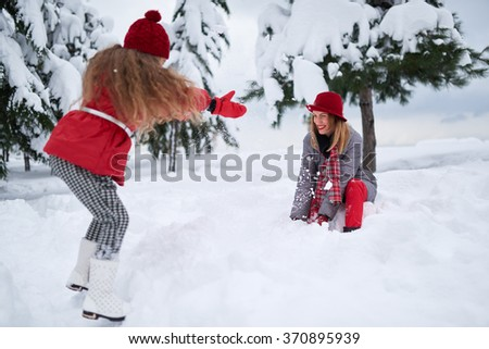 daughter and mother playing with snow in park