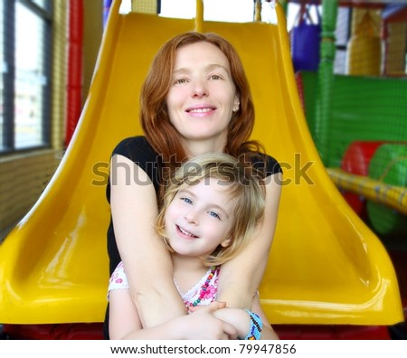 daughter and mother together in playground sitting on yellow slide - stock photo