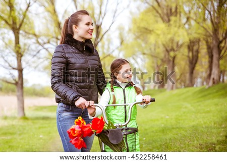 Daughter and mother walk along the shore of the lake in spring Park with a bike and talk. Family values, education