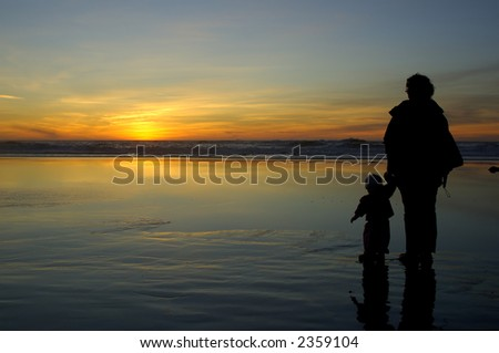 Daughter and mother watch sunset hand in hand at Pacific ocean beach in San Francisco.