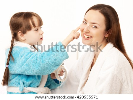 daughter applying cream on her mother's face in bed at home - stock photo