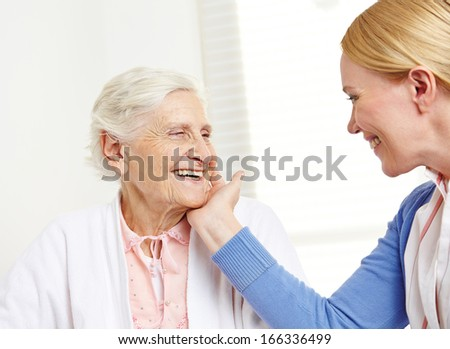 Daughter caressing happy senior mother with her hand over her cheek - stock photo