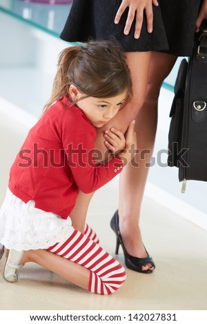 Daughter Clinging To Working Mother's Leg - stock photo