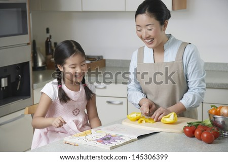 Daughter coloring on kitchen counter and mother cutting bell pepper in the kitchen - stock photo