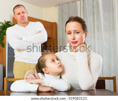 Daughter comforting sad mother and angry father - stock photo