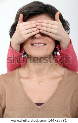 Daughter covering mother's face - stock photo