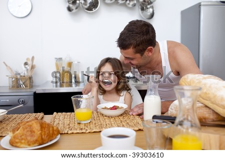 Daughter eating cereals and fruit for breakfast with her father
