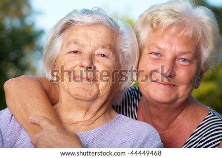Daughter embraces her senior mother. - stock photo