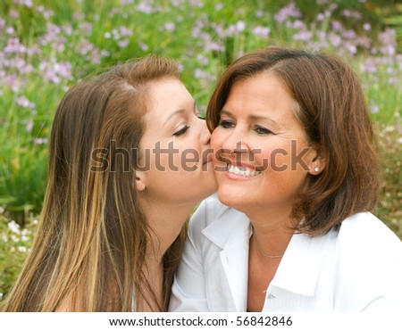 Daughter gives her mom a kiss on the cheek - stock photo