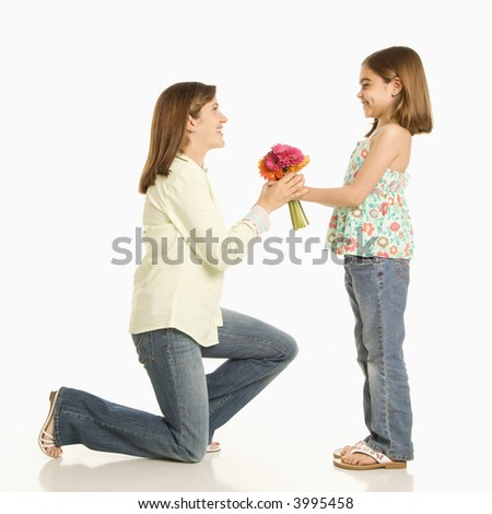 Daughter giving bouquet of flowers to mother. - stock photo