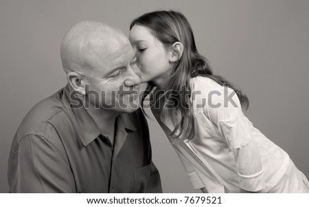 Daughter Giving Father Cute Kiss on Cheek - stock photo