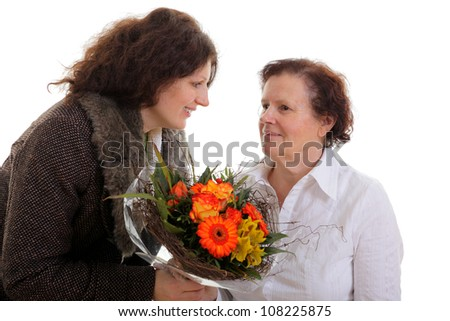 Daughter giving flowers to her mother for mother's day .