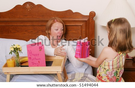 Daughter giving mom a Mothers Day gift - stock photo