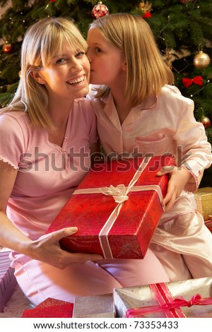 Daughter Giving Mother Christmas Present In Front Of Tree - stock photo