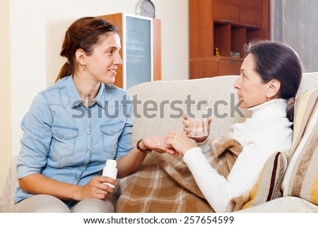 daughter giving the tablets to mature mother at home