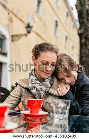 Daughter holding head on mothers shoulder. - stock photo