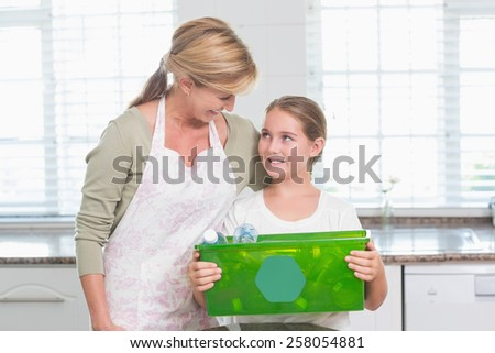 Daughter holding recycling box with her mother at home in the kitchen - stock photo