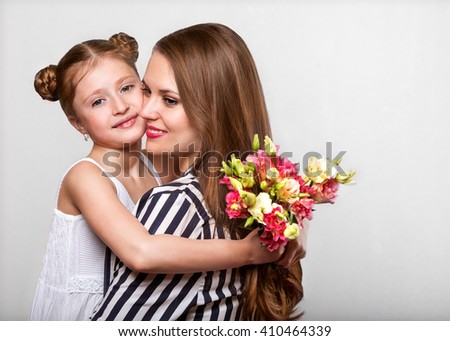 daughter hugging her mother and gives her flowers in the studio, happy mother's day  - stock photo