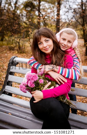 Daughter hugging her mother. autumn. garden - stock photo